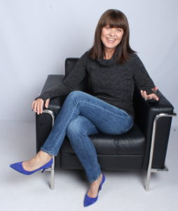 Tamara Parisio. dressed in a dark grey sweater, blue jeans, and bright blue heels, sitting in a black chair along a light grey wall