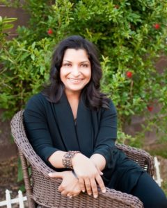 Parul Agrawal in dark green shirt sitting in wicker chair in front of a tree with red flowers